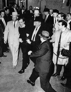 Lee_Harvey_Oswald_being_shot_by_Jack_Ruby_as_Oswald_is_being_moved_by_police,_1963